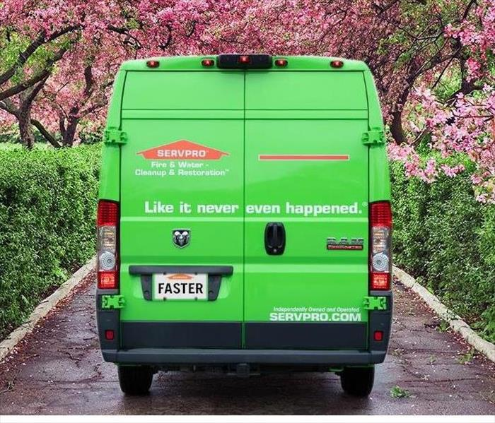SERVPRO van on road with trees in spring