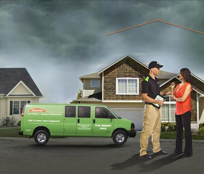 SERVPRO van in front of home with employee and customer